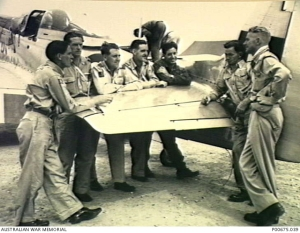 Pilots of the 77 RAAF at Taegu, Korea, standing by the wing of a Mustang