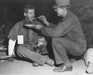 CPL Thomas Edwards, NYC, Co. A, 8th Cav Reg, 1st Cav Div is fed by PFC Cornelius Bosma, Ontario,CA 8063 MASH I Corps