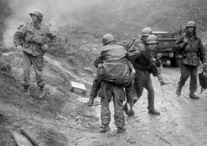 2nd Div. soldiers are carried on the backs of other G.I.s from Heartbreak Ridge to an aid station