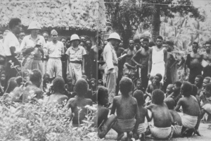 Japanese soldiers teach New Guinea villagers songs as part of their indoctrination.