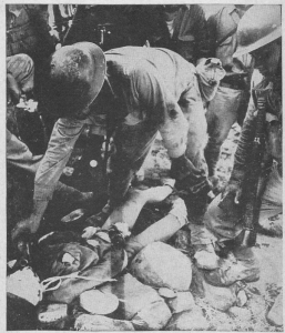 US officer giving water to a wounded Japanese soldier