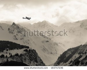 stock-photo-vintage-wwii-airplane-flying-over-mountain-peaks-in-southeast-alaska-183747236
