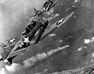 Dauntless divebombers from the USS Hornet approach the burning cruiser IJN Mikuma
