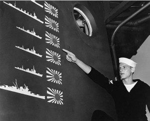 sailor points to the USS Boise's scoreboard