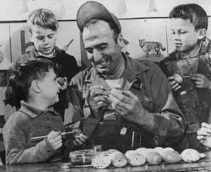 Sgt. George A. Crist, 1st cook, US 8th AF/96th Bombardment Group, teaches British lads the art of Easter egg decorating.