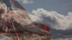 stock-footage-slow-motion-american-flag-with-time-lapse-clouds