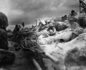 Marines take cover behind a seawall.