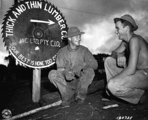 Pvt. Arthur Ristinen of Menagha, Minn., and Pfc. John Weinzinger of Phillips, Wisconsin, 186th Inf. Reg., 41st Inf. Div., relax in front of Warisota Plantation sawmill run by men of the 186th. Sawmill was used to obtain lumber for bridge construction on the new Oro Bay Dobodura road, New Guinea. (5 May 43) Signal Corps Photo: GHQ SWPA SC 43 5816 (T/4 Harold Newman)