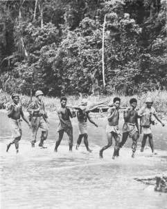 New Guinea natives evacuate wounded Allies across the Driniumor River near Afua.