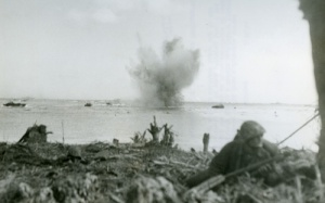 While marines crawl onto a beach, an enemy shell explodes a troop-laden amtrac offshore. Survivors from other shelled amtracs are swimming toward the beach. (National Archives)