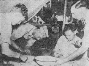 T/5 Robert Kingston, Maj. Robert E. Pennington, Lt. E. Boyd (seated) and T/5 Joseph H. Hill operating on Chinese soldier on Salween Front.