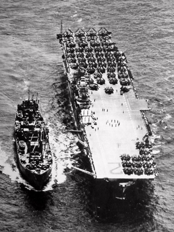 Overhead view of an ammo ship replenishing USS Hornet (CV-12), October 1944. Note the forward antenna masts half way up.
