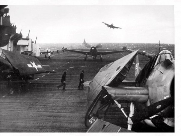A VF-11 F6F getting a wave off while another Hellcat taxies out of the way, Dec. 1944 on USS Hornet (CV-12).